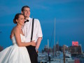bride and groom standing by the Baltimore waterfront with the Dominos sign in the background