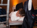 child sleeping on chairs at wedding