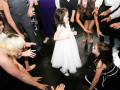 flowergirl surrounded by guests on the dancefloor at wedding