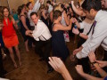 bridesmaid and groomsmen dancing back to back, surrounded by wedding guests