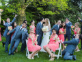 bride and groom kissing, surrounded by silly wedding party
