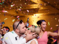 bride and groom kissing while confetti falls in the background